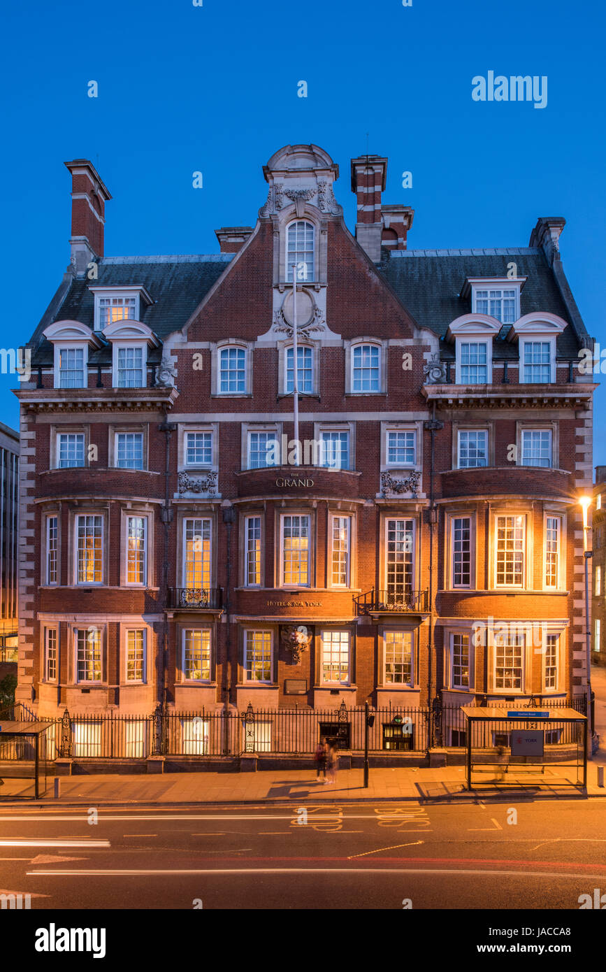 Evening view of The Grand Hotel & Spa, (5-star luxury hotel) with a golden glow from street lights & behind - Stock Image
