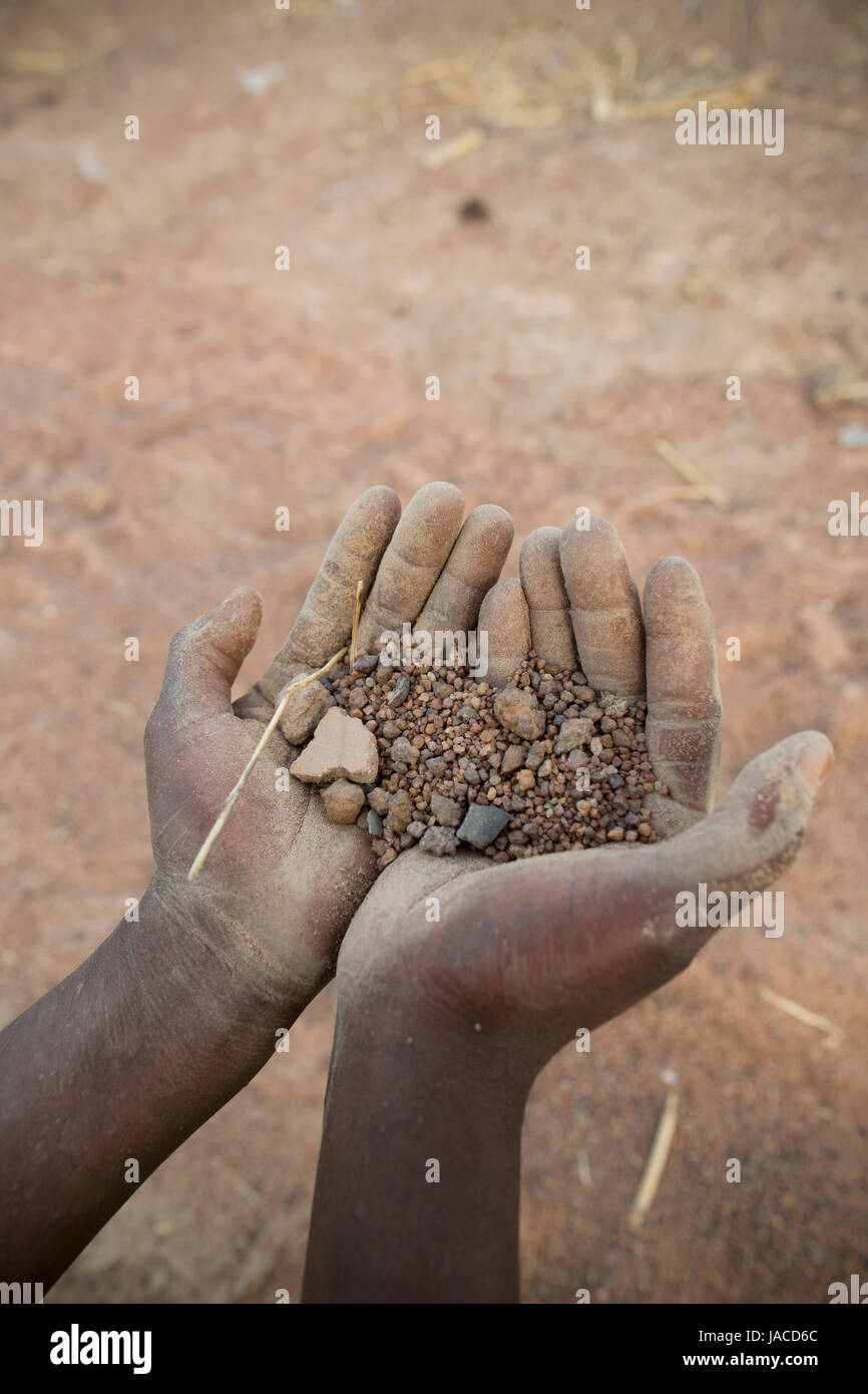 Hands hold dry, parched soil in drought-stricken northern Ghana, West Africa. - Stock Image