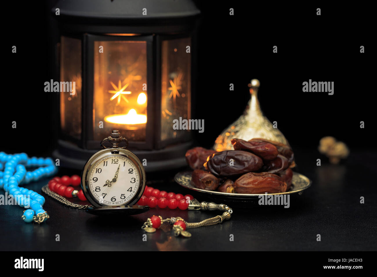 Ramadan concept with dates, pocket watch, rosary and lantern in darkness - Stock Image