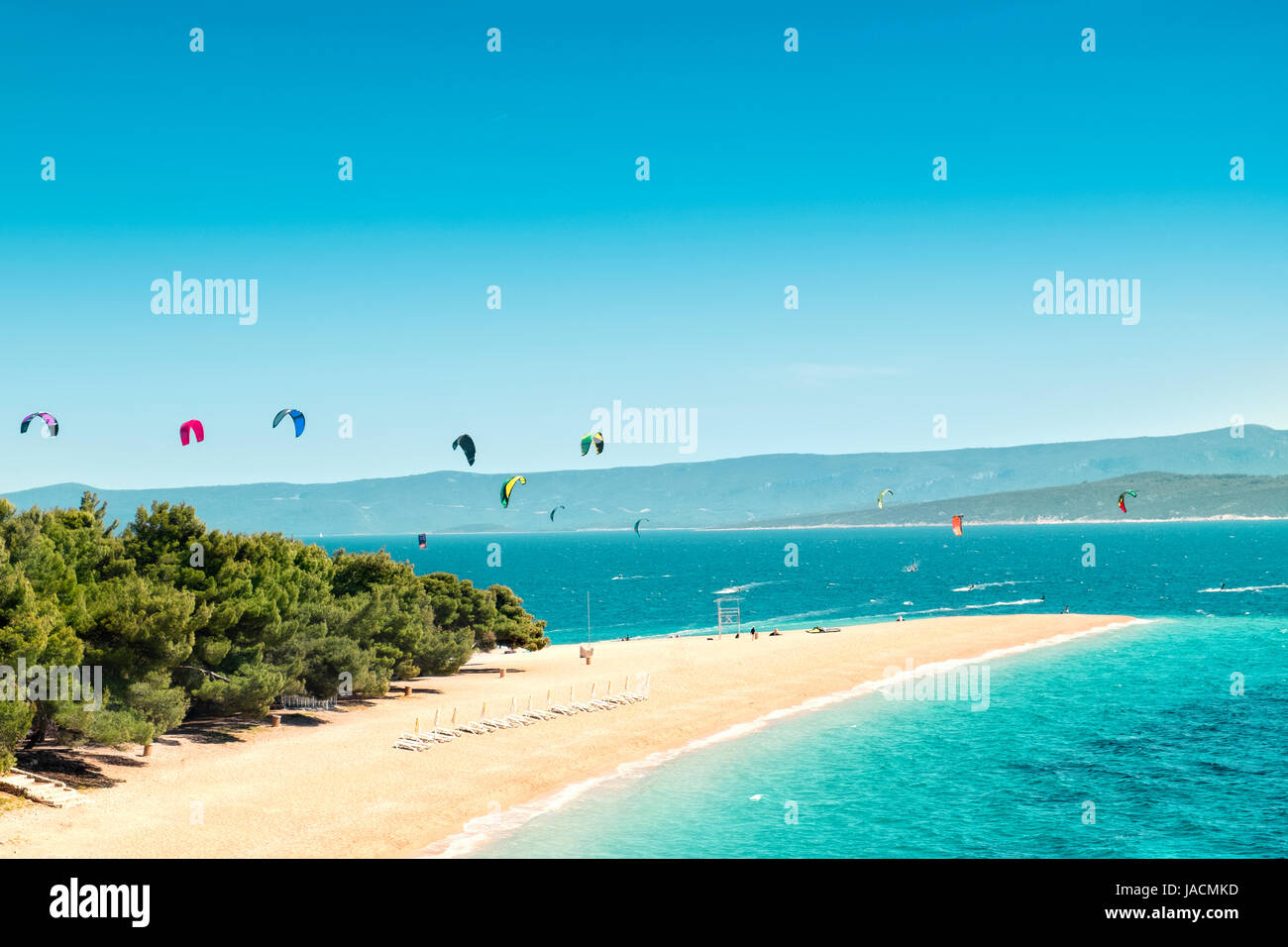 View of the landmark Golden Horn at the island Brac in Croatia. Kitesurfer and windsurfer in the background enliven - Stock Image