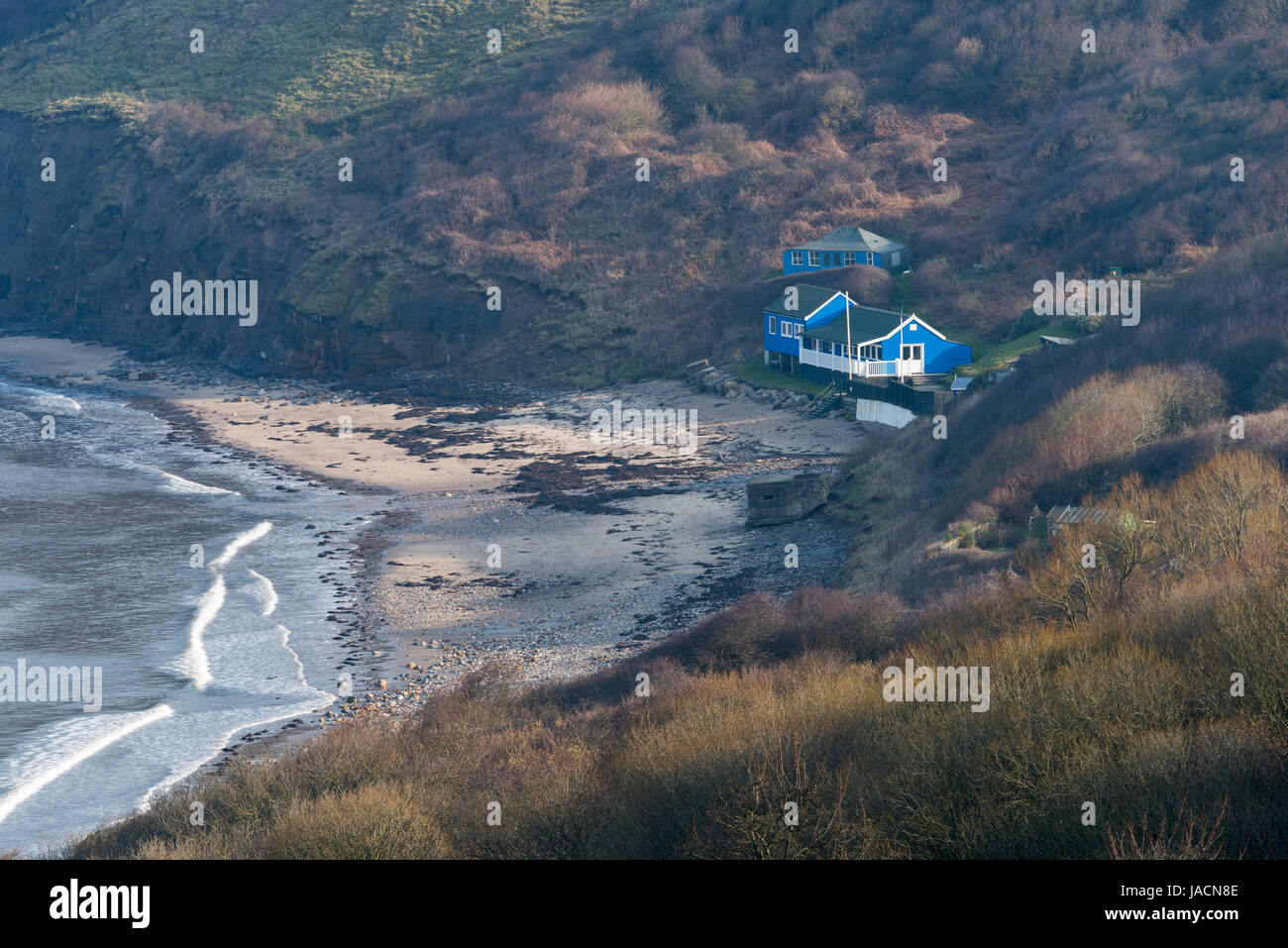 High view over Runswick Bay Beach and Sailing Club clubhouse, nestling under cliffs & on the beach, near the - Stock Image
