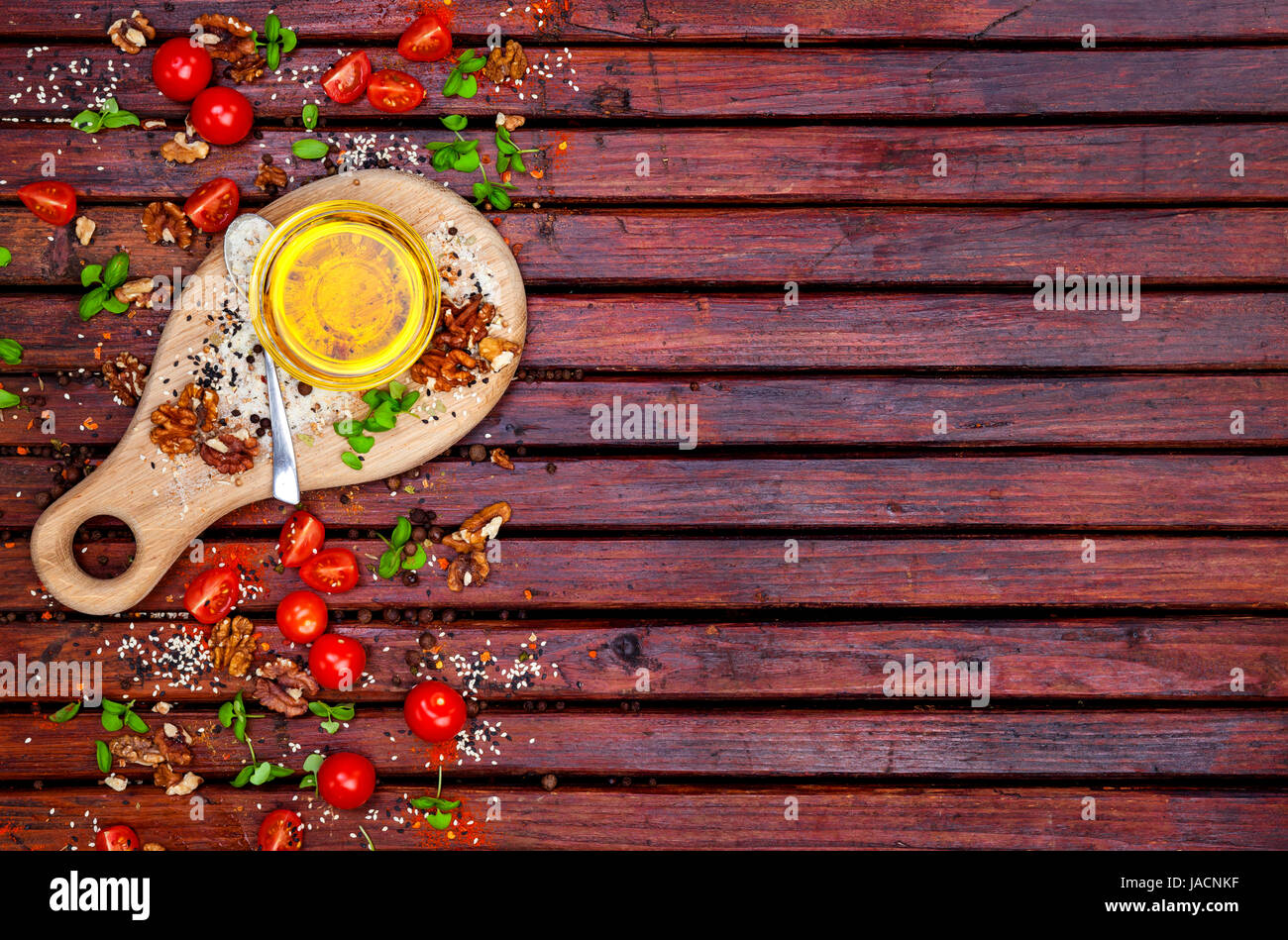 Food background with copy space. Spices, cherry tomatoes, basil and vegetable oil on dark wooden table, top view Stock Photo