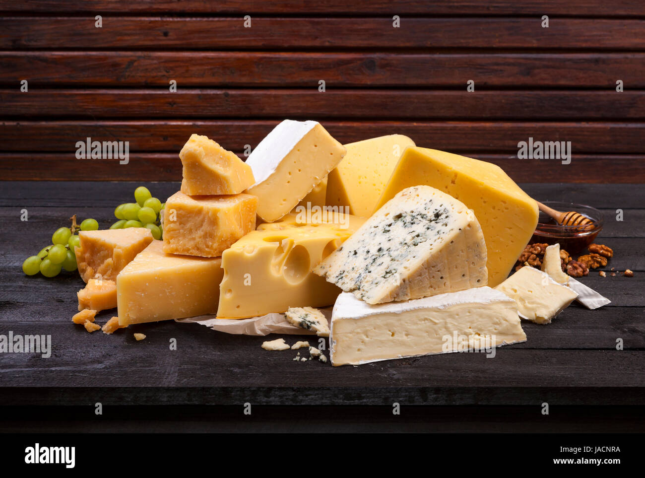 Cheese on black wooden table. - Stock Image