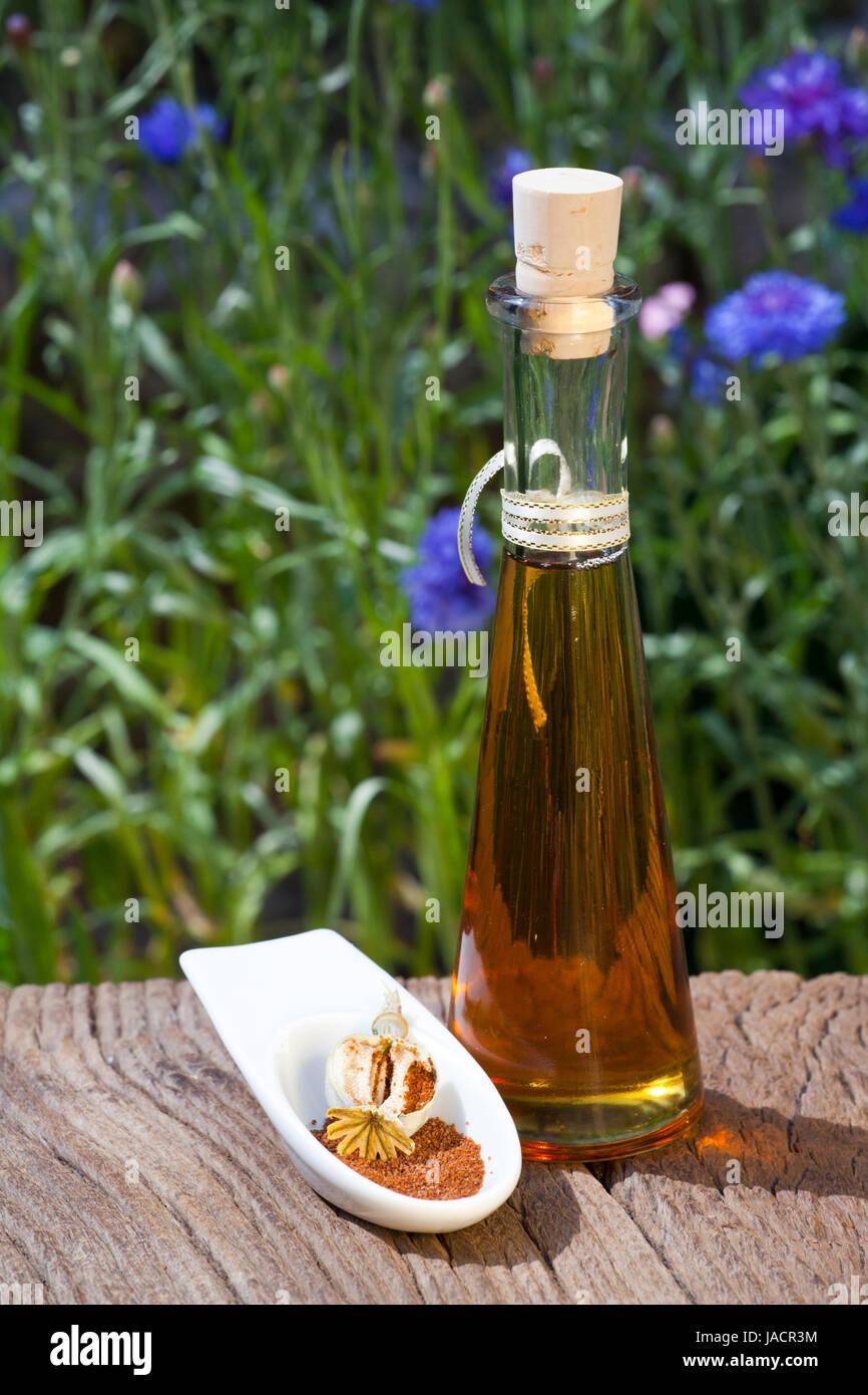 Eine kleine Schale mit Mohnsamen und eine Flasche Mohnöl stehen auf einem alten rustikalem Holztisch - Stock Image