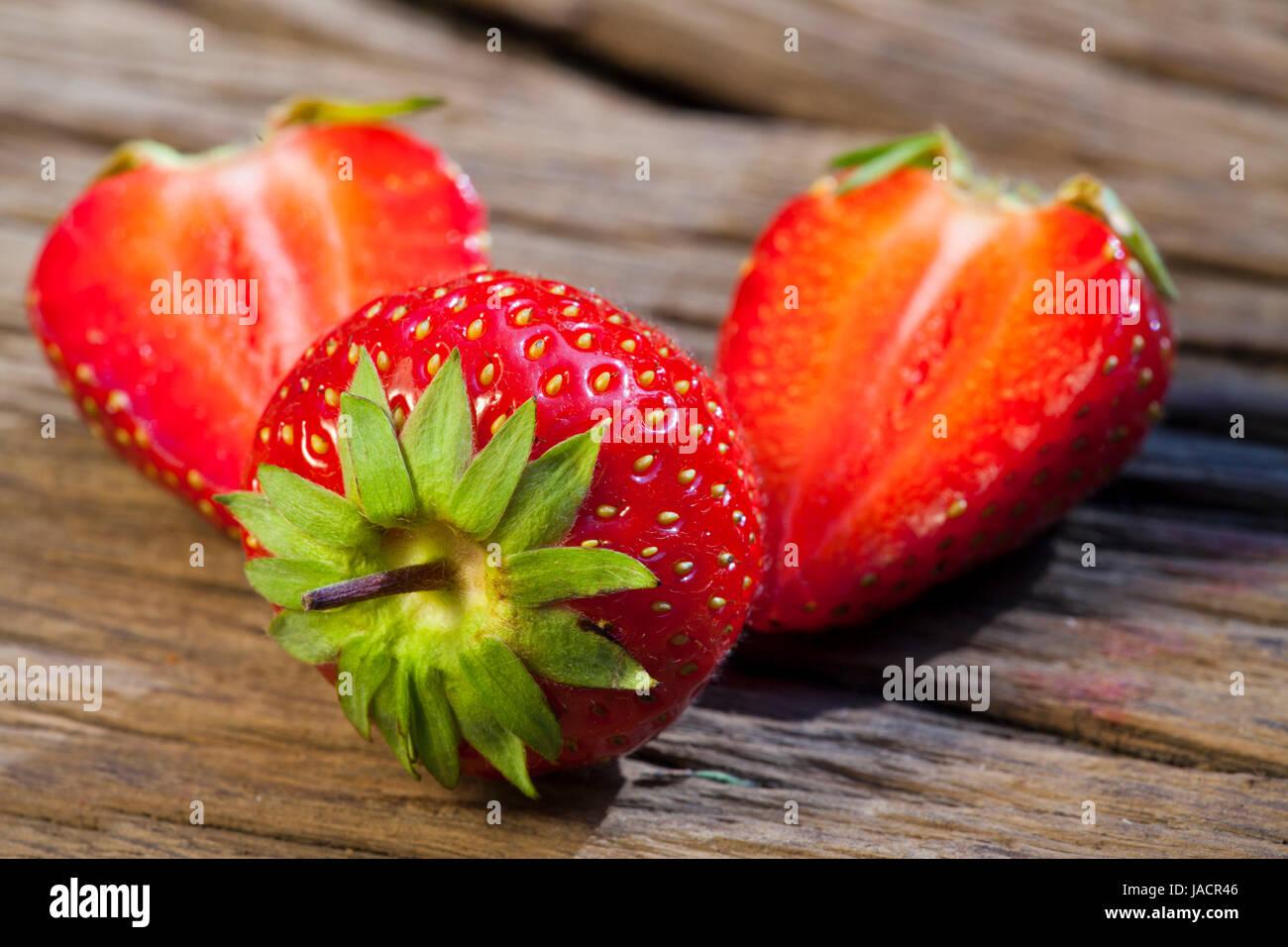 Frische Erdbeeren der Saison, eine ganze und zwei halbe auf einem Holzuntergrund - Stock Image