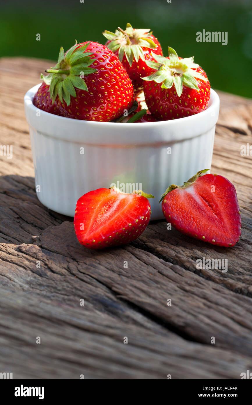 Leckere frisch Erdbeeren in einer weißen Porzellanschale auf einem rustikalem Holztisch mit Textfreiraum im - Stock Image