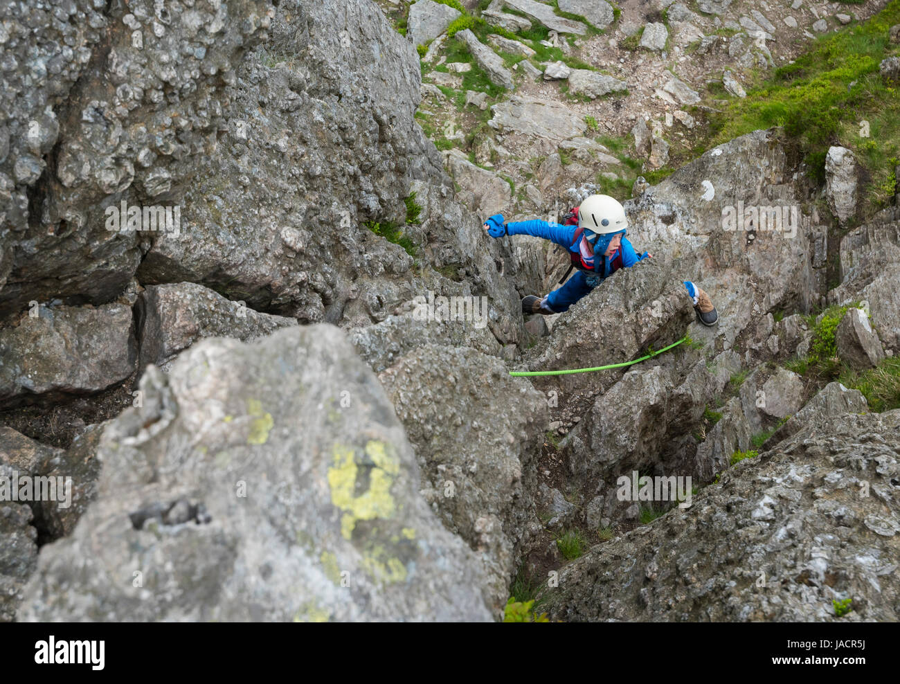 A young boy srambling on the north ridge of Tryfan, Snowdonia - Stock Image