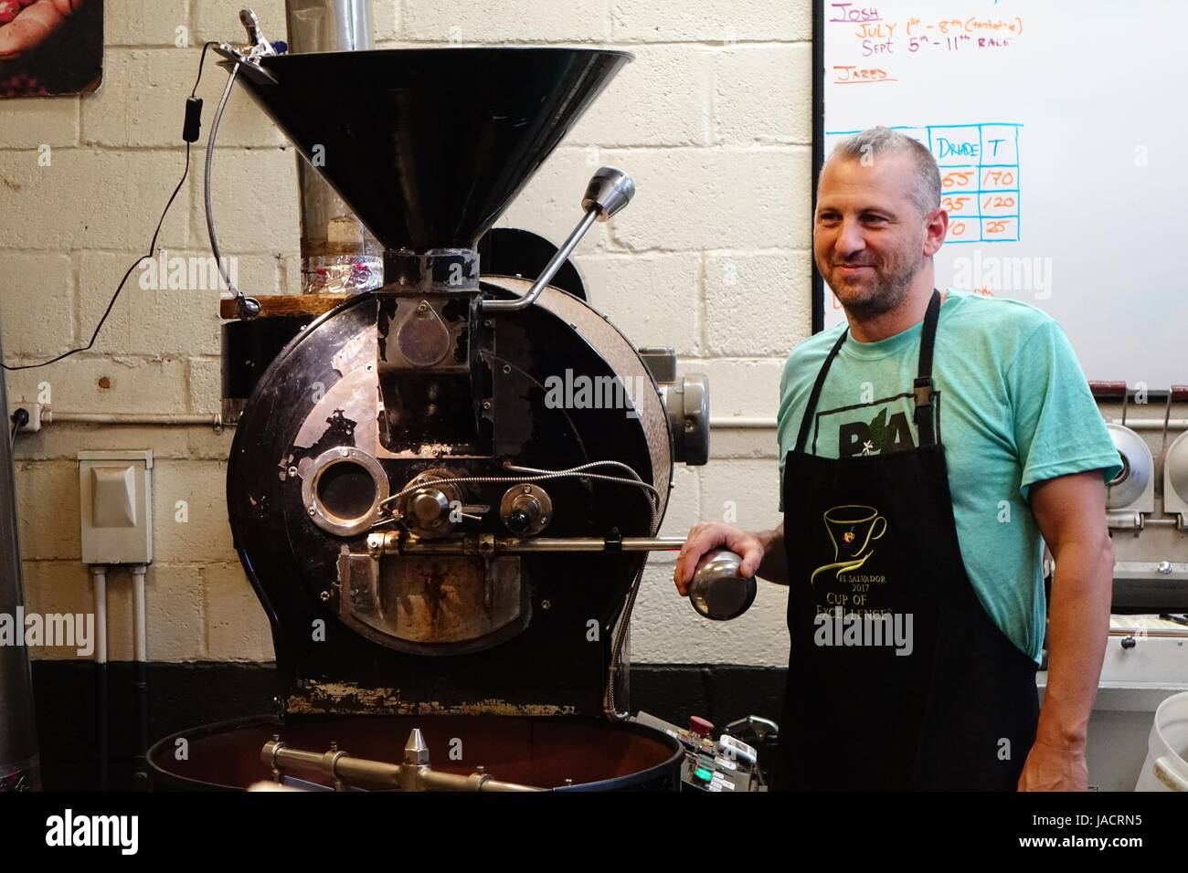 Scott Cornary, owner of Carrboro Coffee Rosters and the Open Eye Café, describes the process of roasting coffee - Stock Image