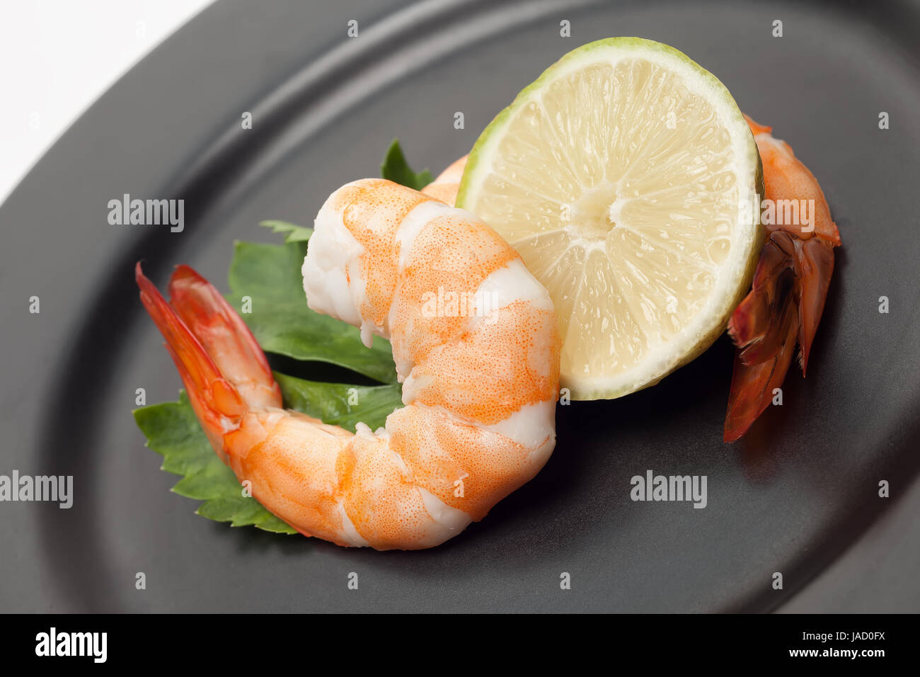 Shrimp with lime on black plate - Stock Image