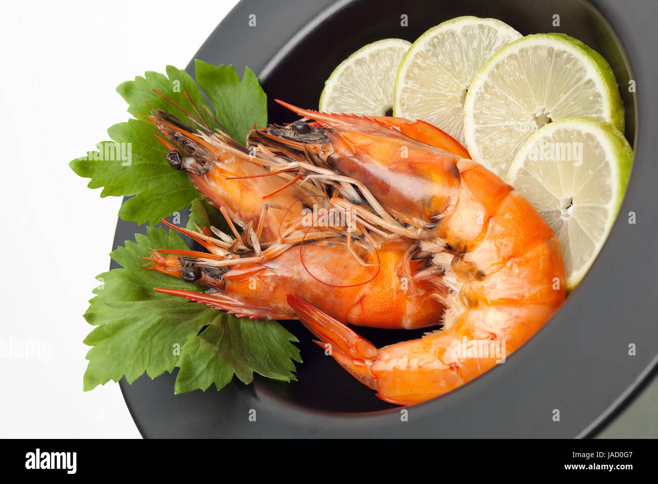 Grilled shrimp with lime on black plate isolated on white background - Stock Image