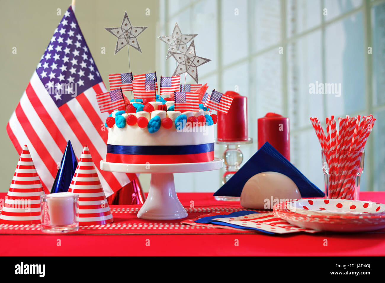 USA National holiday celebration party table with showstopper cake and flags. - Stock Image