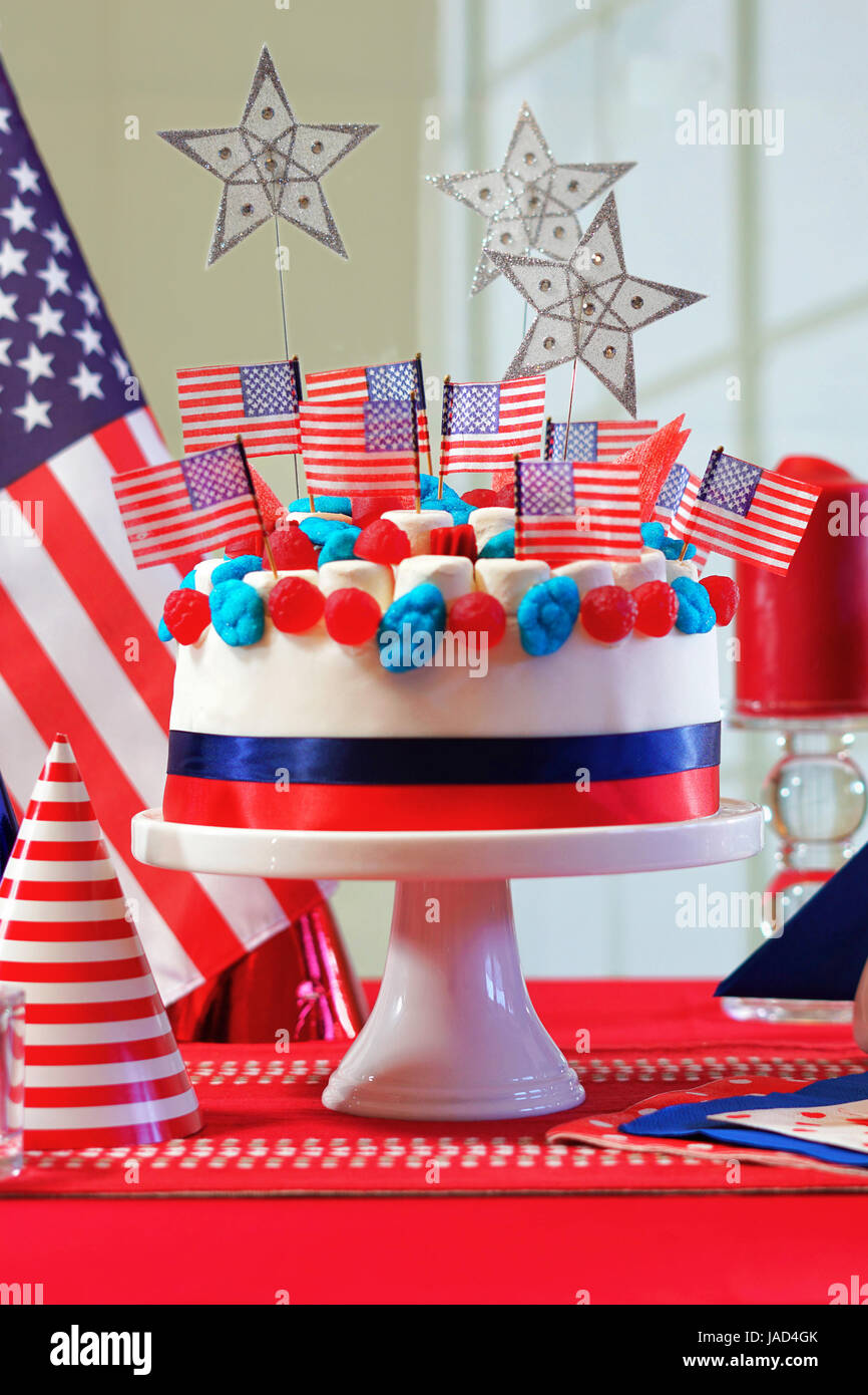 USA National holiday celebration party table with showstopper cake and flags, vertical. - Stock Image