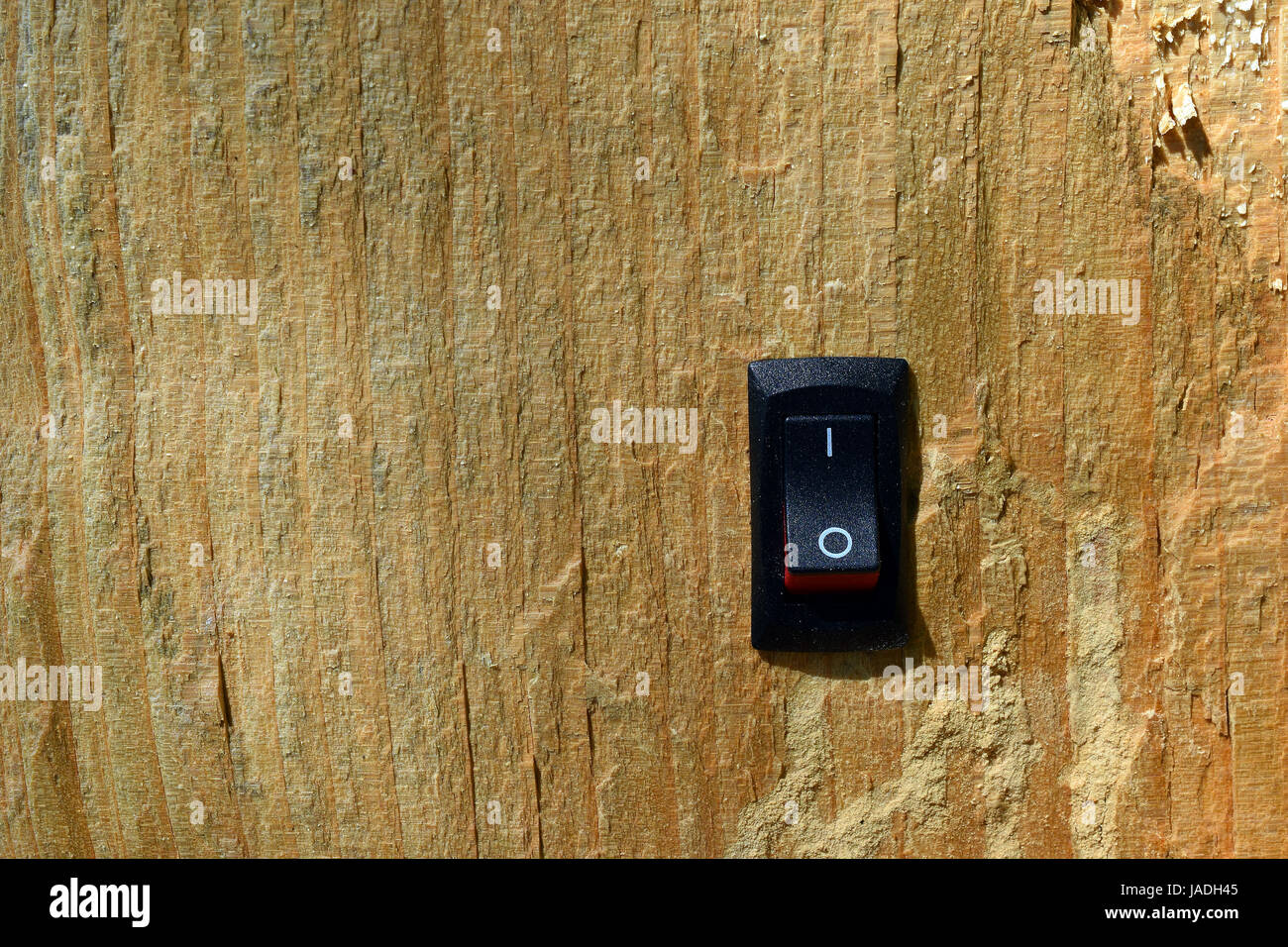 Power switch inserted on wood. Conservation, green business and alternative energy concept. - Stock Image