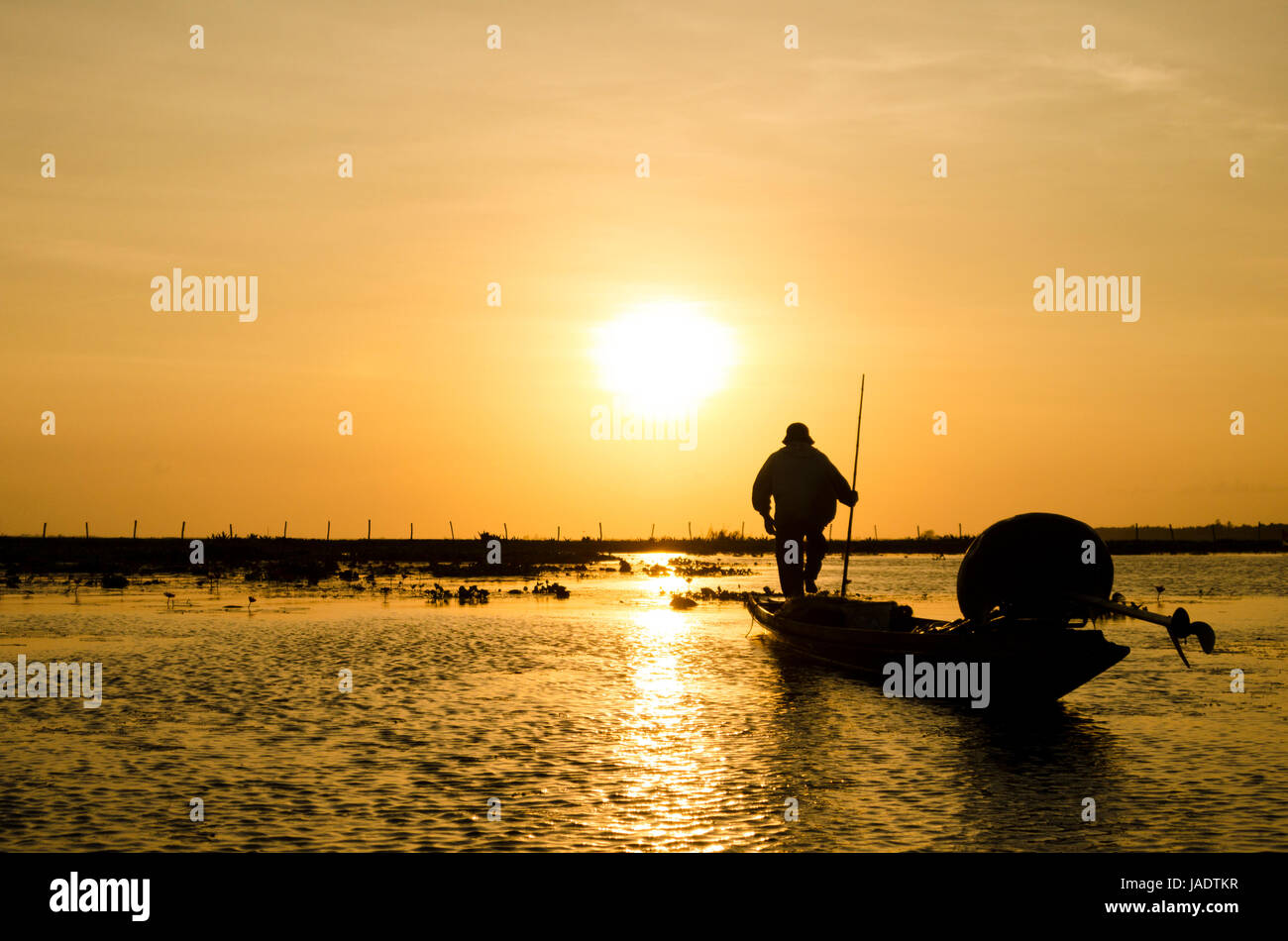 Fisherman going out on a small fishing boat in the early morning to put out fishing net in the local reservoir down - Stock Image