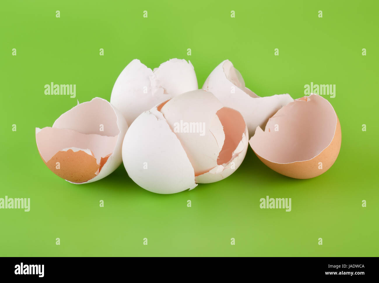 Group pieces of egg shell on a green background - Stock Image