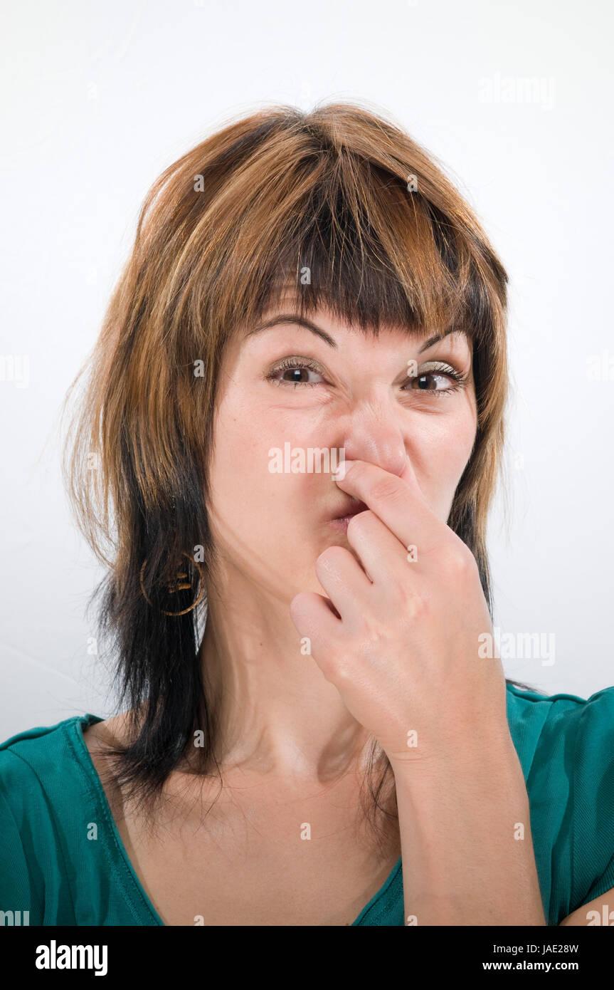 Kopf-und-Schulter-Aufnahme einer jungen Frau mit Blick in die Kamera sich die Nase zuhaltend Stock Photo