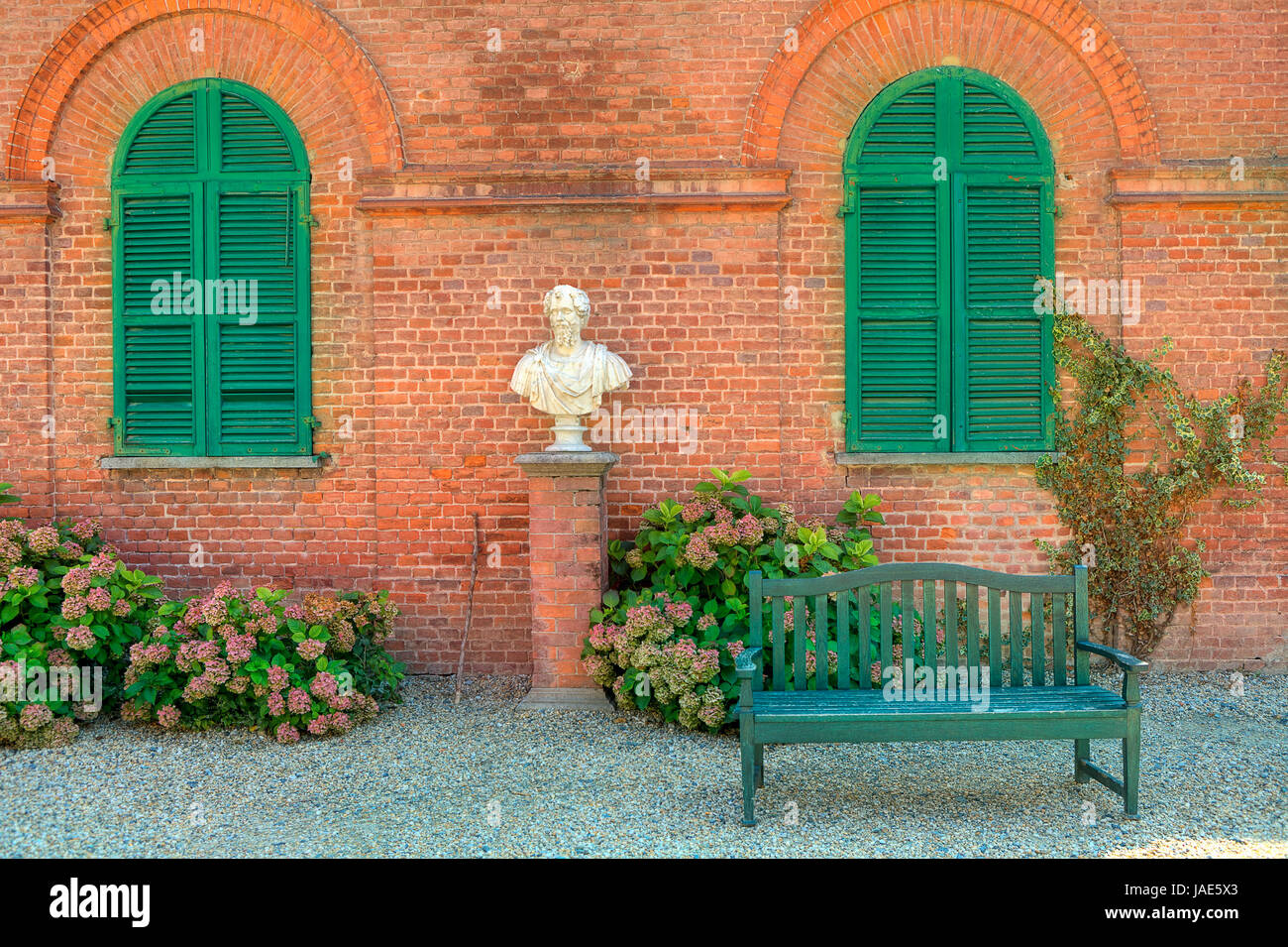Attractive Wooden Bench Stand On The Gravel In Front Of Red Brick House With Closed  Green Shutters In Park Of Racconigi In Piedmont, Northern Italy.
