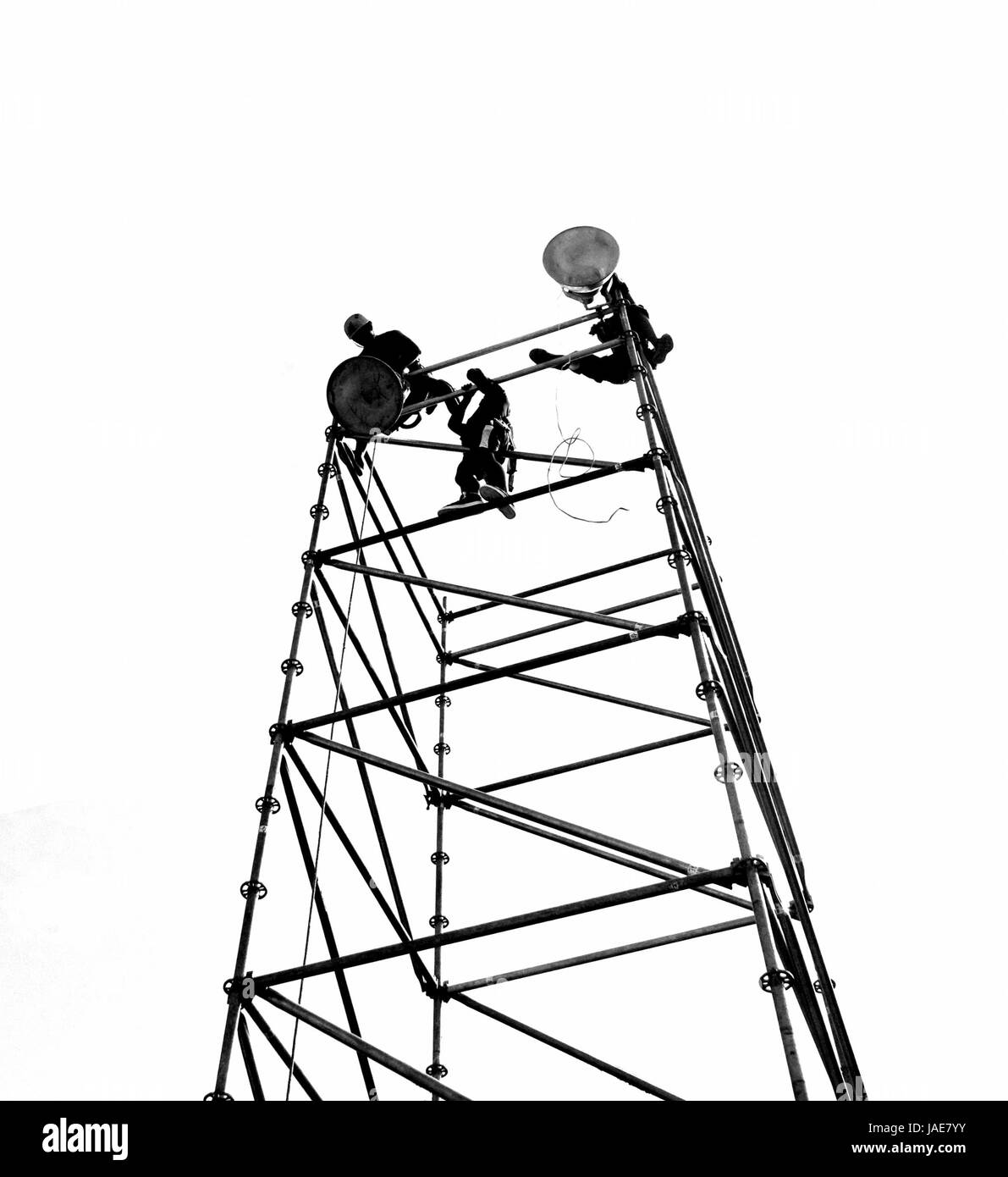 Workers set up powerful lights on scaffolds, seen in silhouette Stock Photo