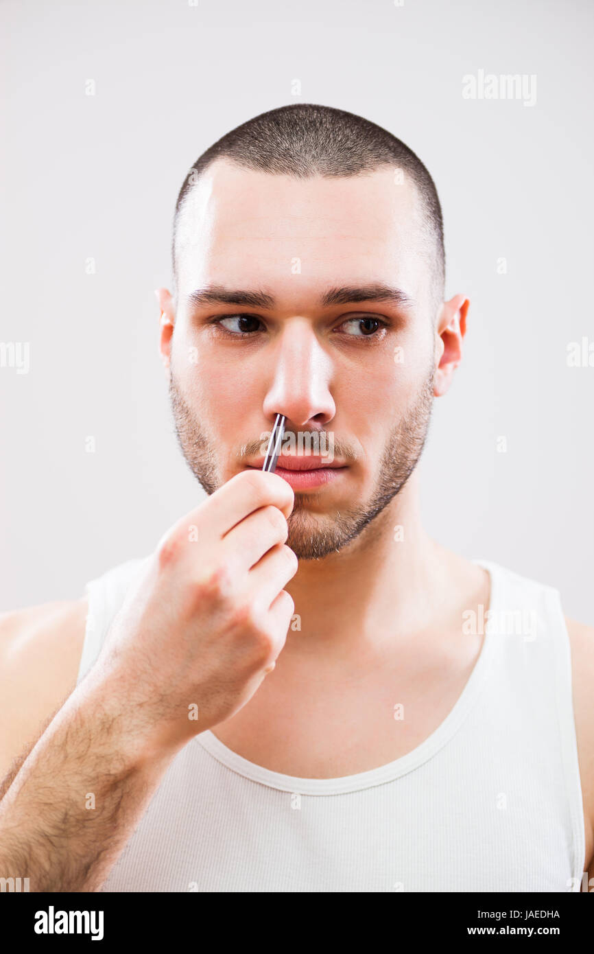 Young man is plucking nose hair with tweezers.