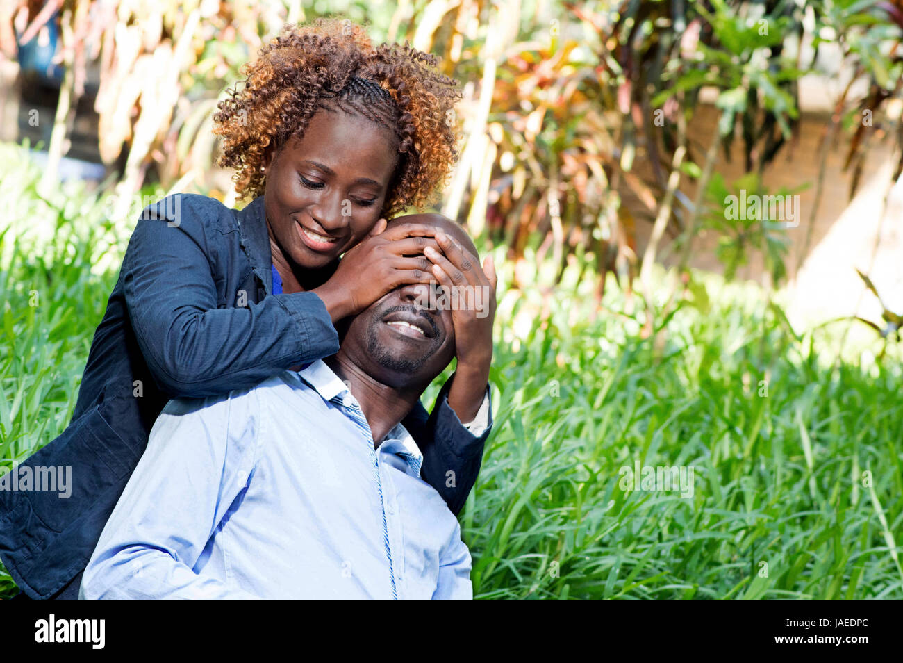 young woman played the guessing game with her lover in him closing his eyes. - Stock Image