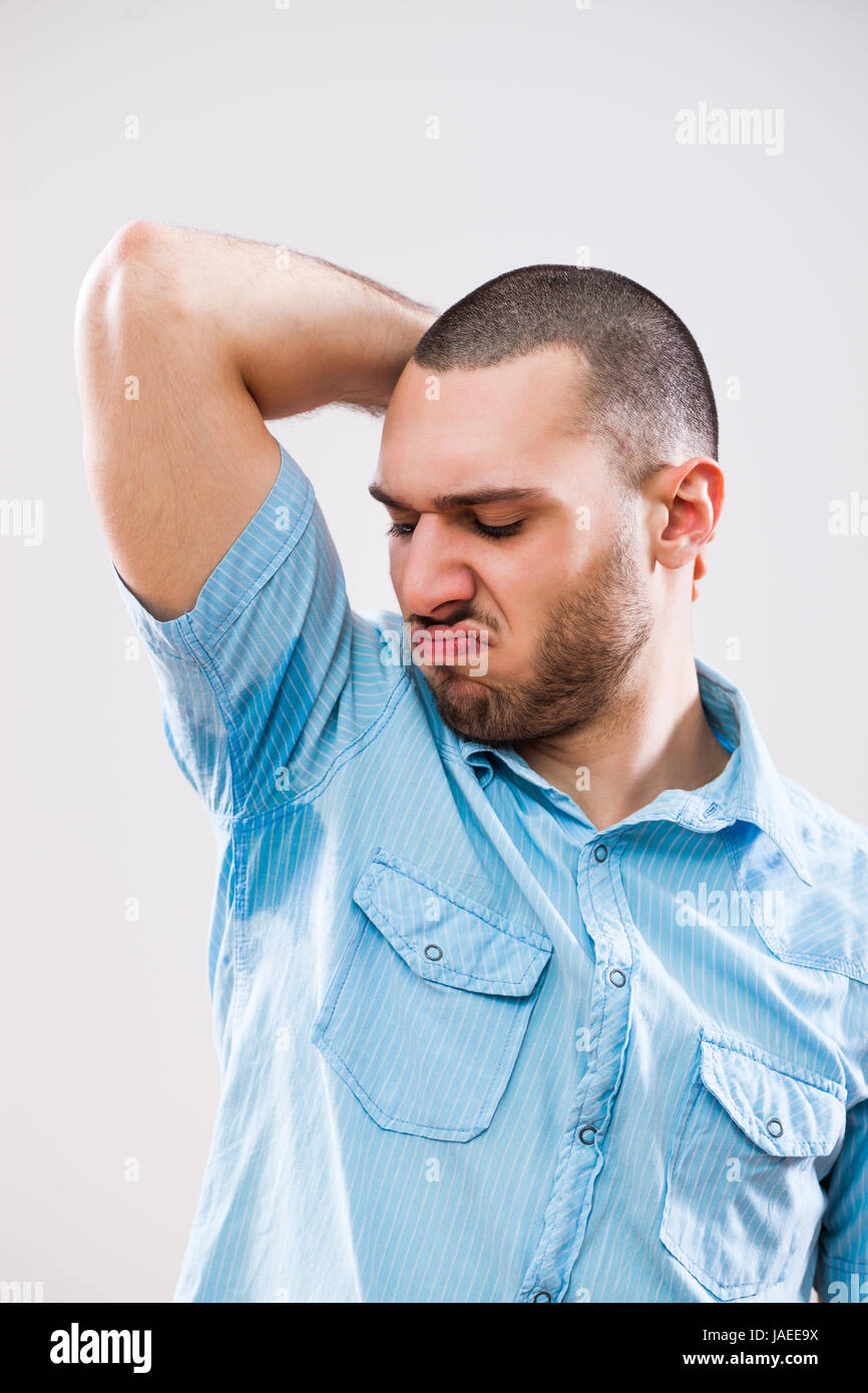 Young man is sweaty and he disgusts unpleasant smell. - Stock Image