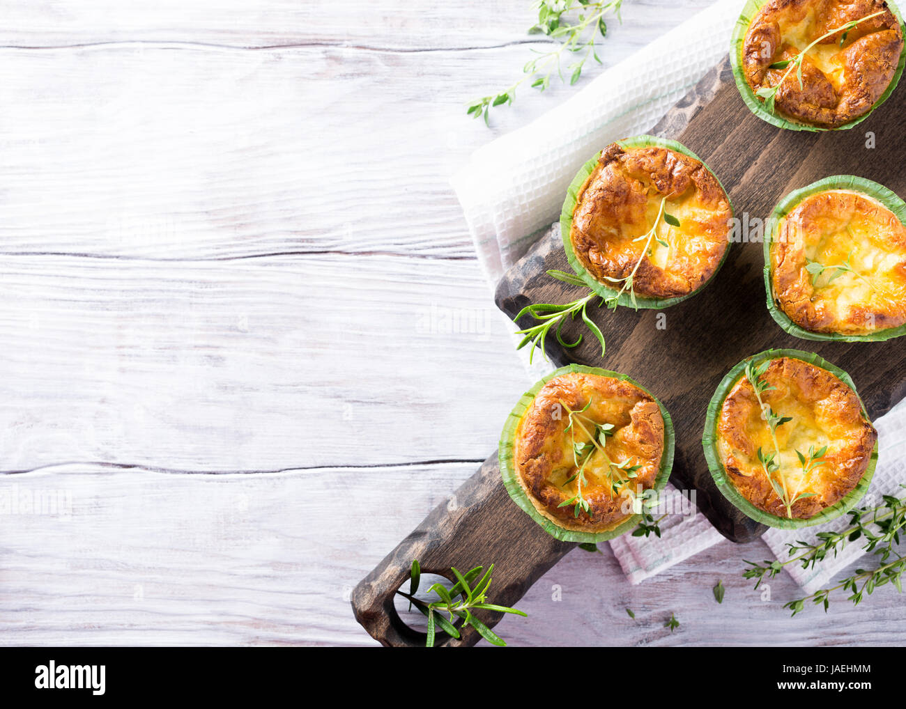 Savory cheddar cheese and leek mini quiches with thyme on dark wooden cutting board. Top view with copy space - Stock Image