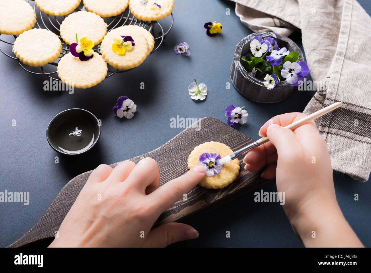 Process of making shortbread cookies with edible flowers on old wooden background. Holiday food - Stock Image