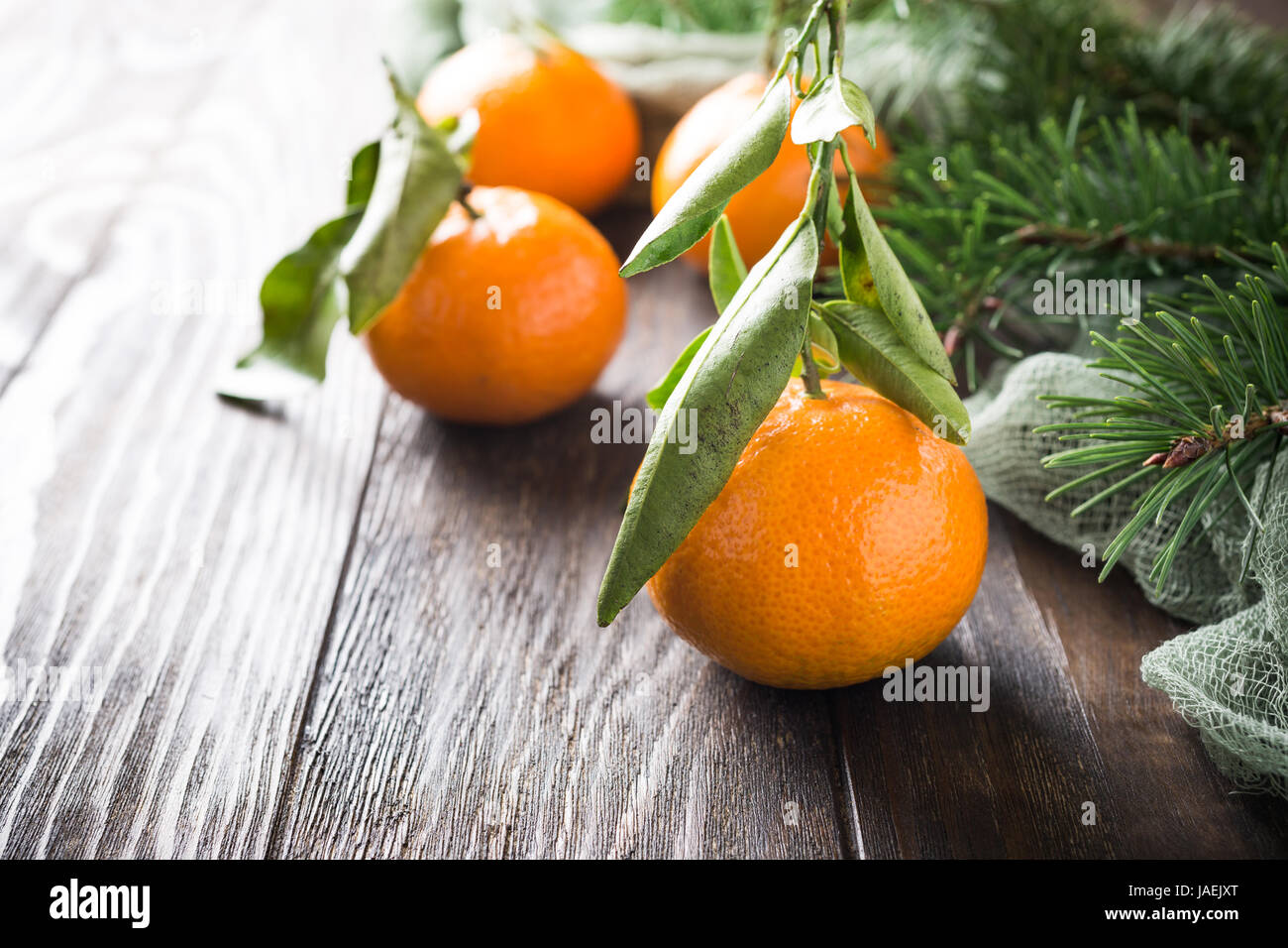 Fresh tangerines with leaves and ripe mandarins on wooden table - Stock Image
