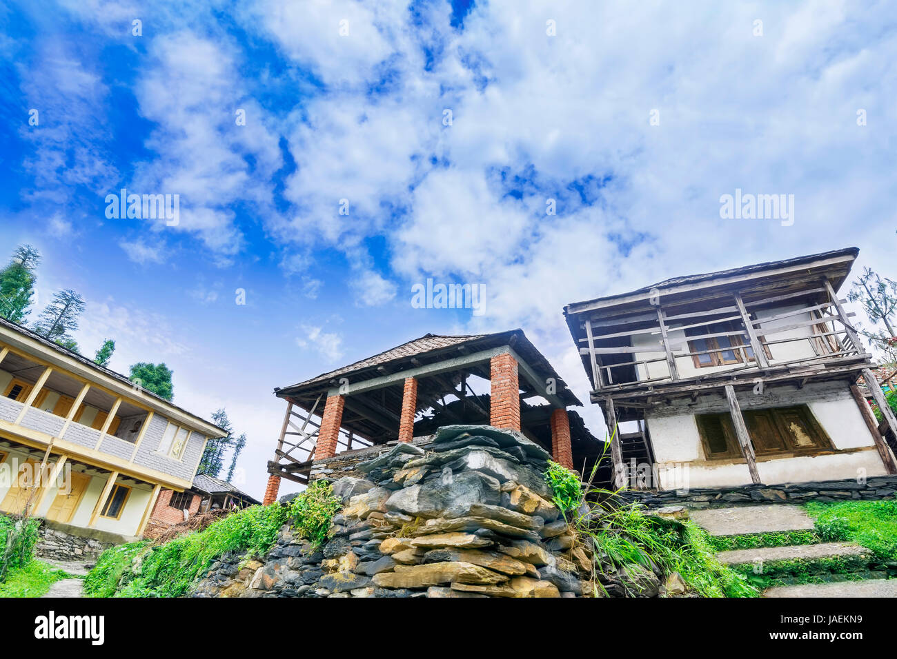 Old and new abandoned wooden houses surrounded by beautiful nature and rocks on top of a hill in a tiny village - Stock Image