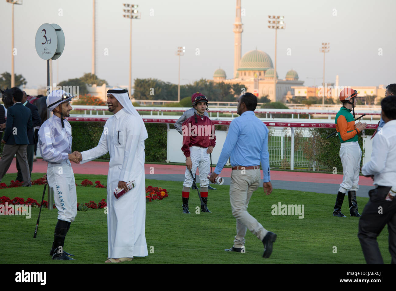 Jockeys and racehorse owners in the paddock before a race at the Racing and Equestrian Club in Doha, Qatar. Stock Photo