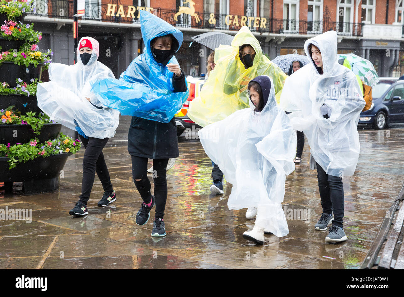 Windsor, UK. 6th June, 2017. Tourists make their way towards Windsor Castle in heavy rain with umbrellas and assorted - Stock Image