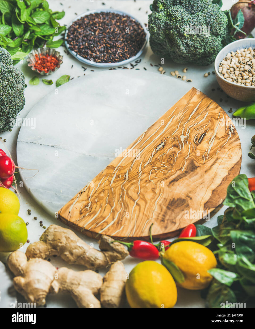 Clean eating healthy cooking ingredients. Vegetables, beans, grains, greens, fruit, spices over grey background, - Stock Image