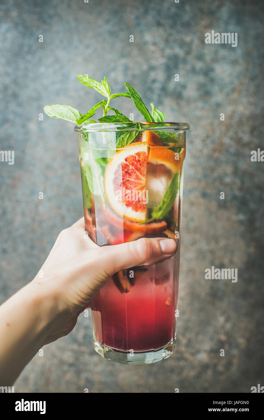 Woman's hand holding glass of blood orange citrus lemonade with mint and ice, dark brown stone background. Refreshing - Stock Image