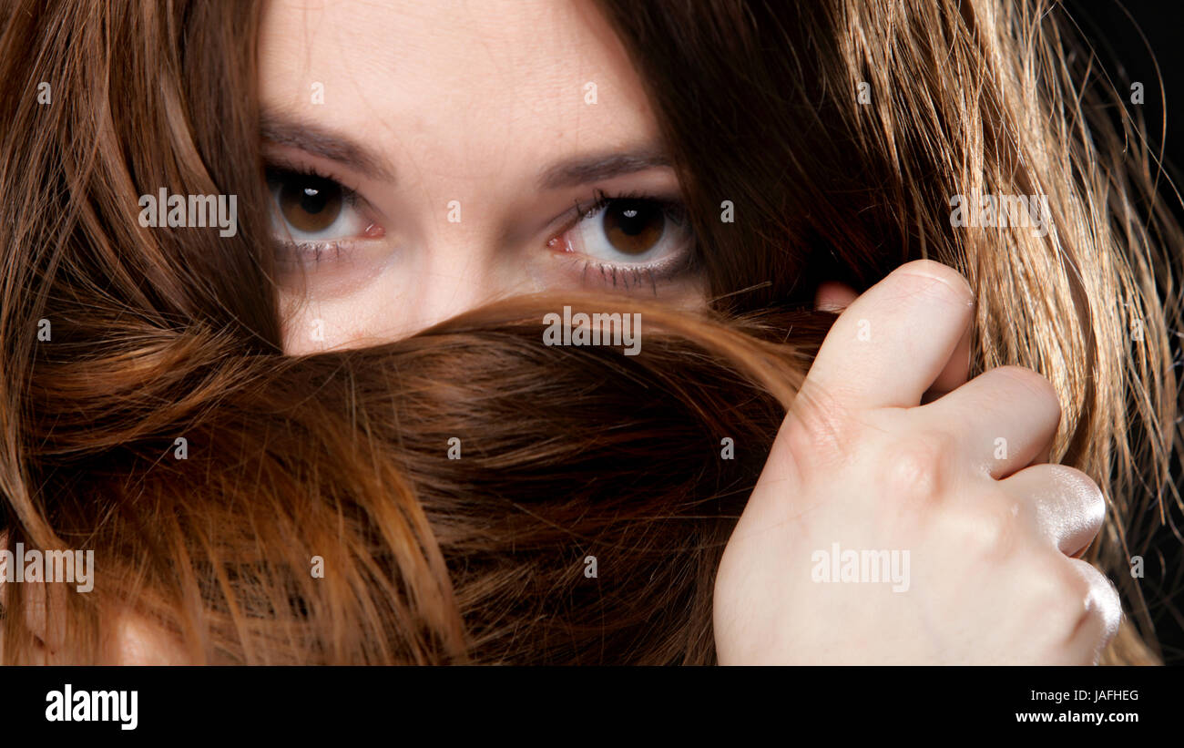 Close-up portrait of a beautiful woman covers the face by long brown hairs Stock Photo