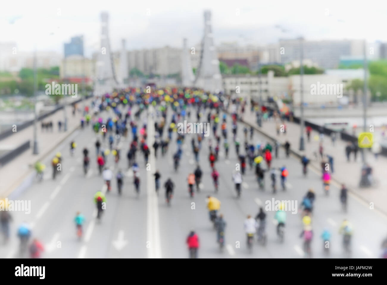 Abstract blurred background of mass urban cycling marathon. Cyclists go to the bridge, back to us. Concept of Sport, - Stock Image