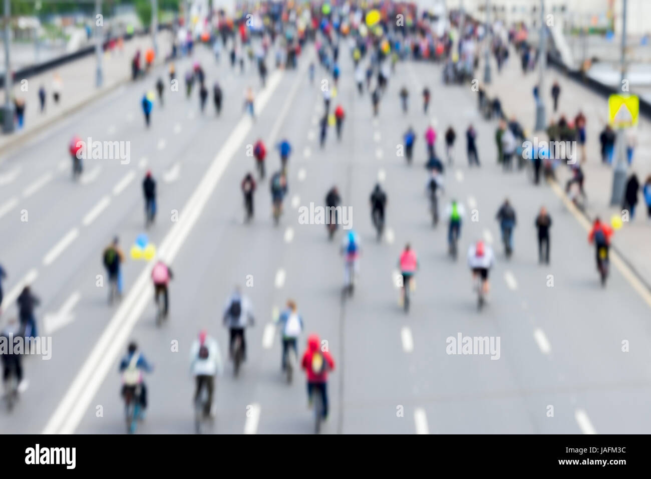 Abstract blurred background of mass cycling marathon in streets of city. Participants go back to us. Concept of - Stock Image