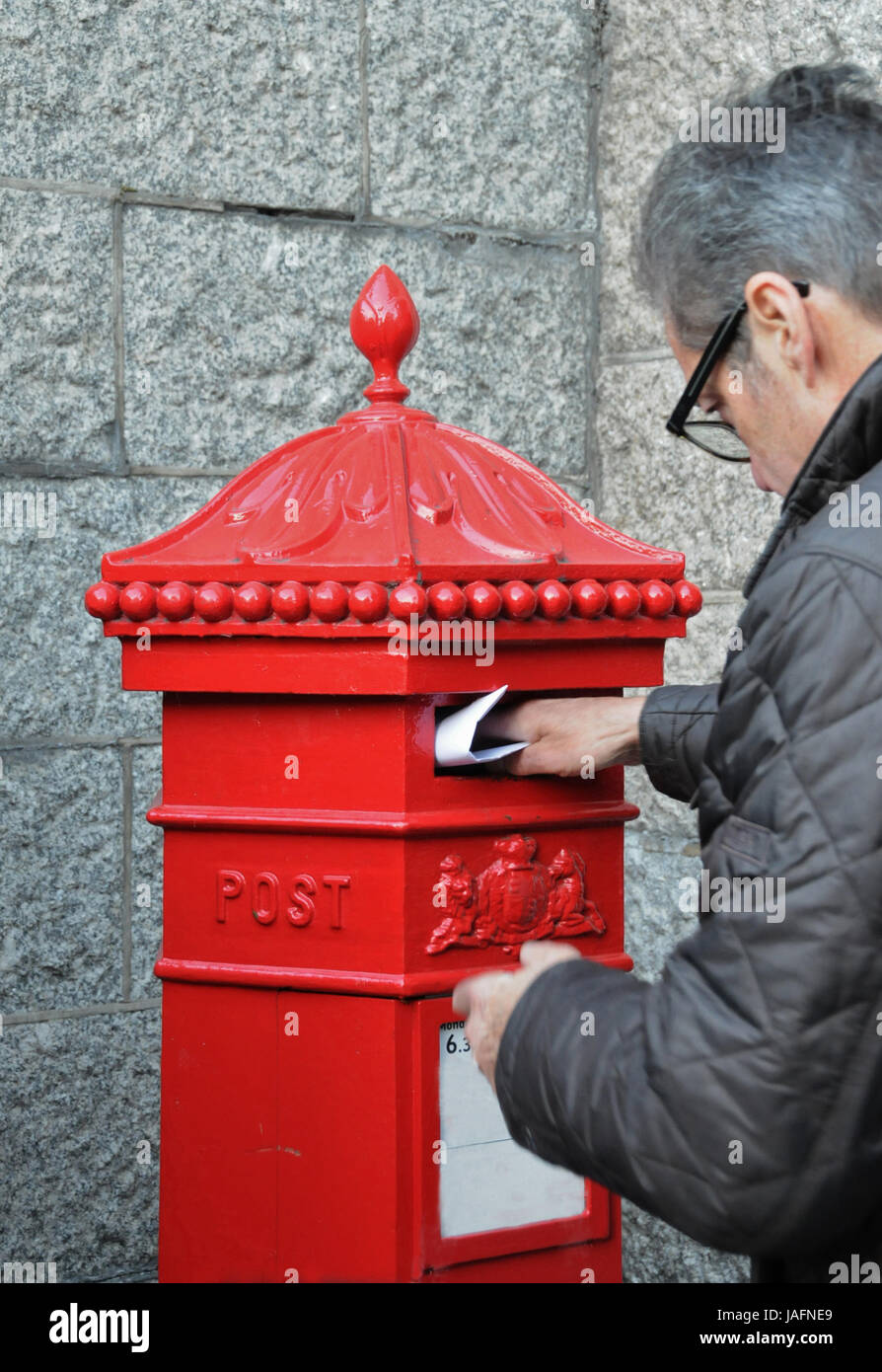 Man posting a letter in a Victorian post box Stock Photo