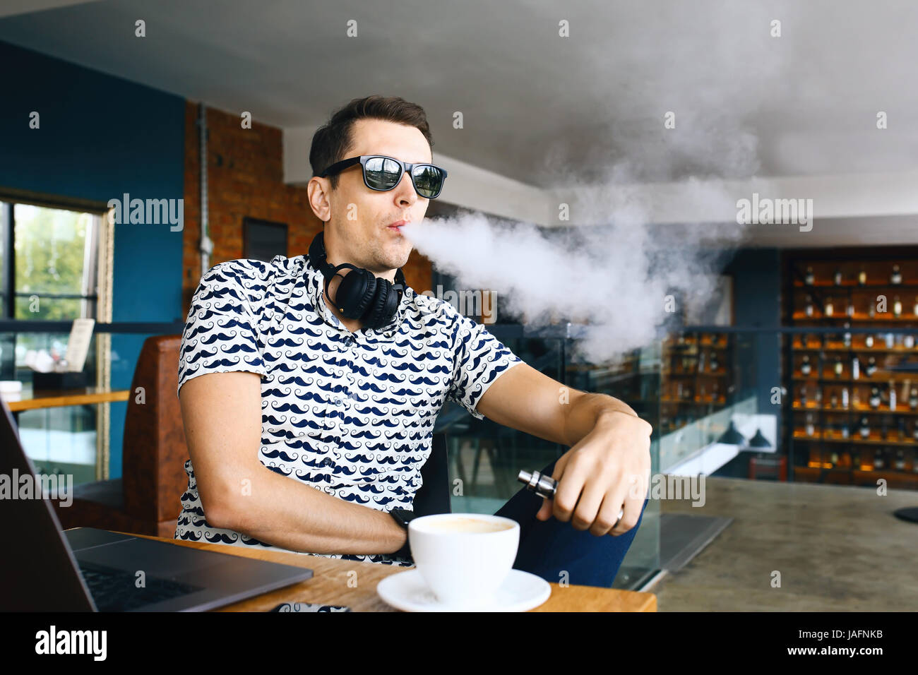Young handsome hipster man with beard sitting in cafe with a cup of coffee, vaping and releases a cloud of vaporsitting. - Stock Image