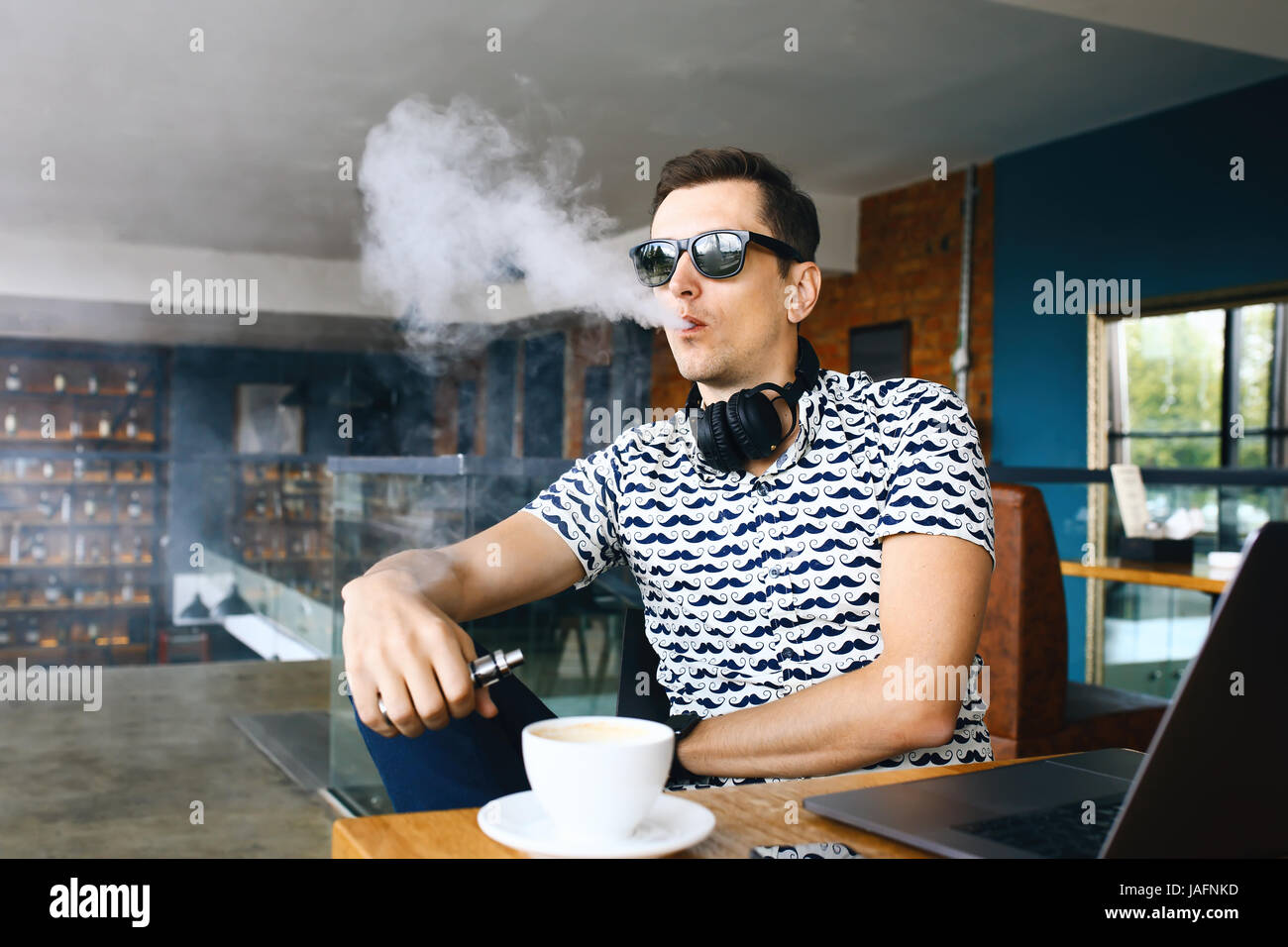 Young handsome hipster man with beard sitting in cafe with a cup of coffee, vaping and releases a cloud of vaporsitting. Stock Photo