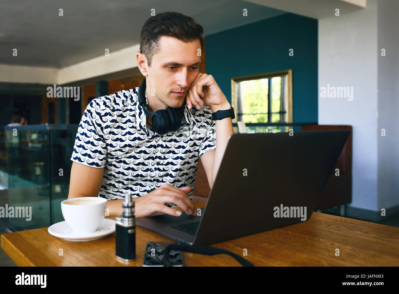 Attractive male worker is using computer in cafeteria - Stock Image