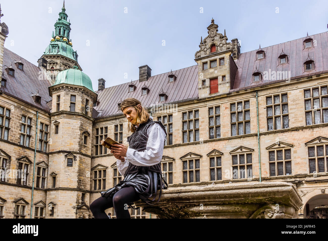 Actor performing prince Hamlet and reads a book at Kronborg Castle, Elsinor, Denmark, May 26, 2017 - Stock Image