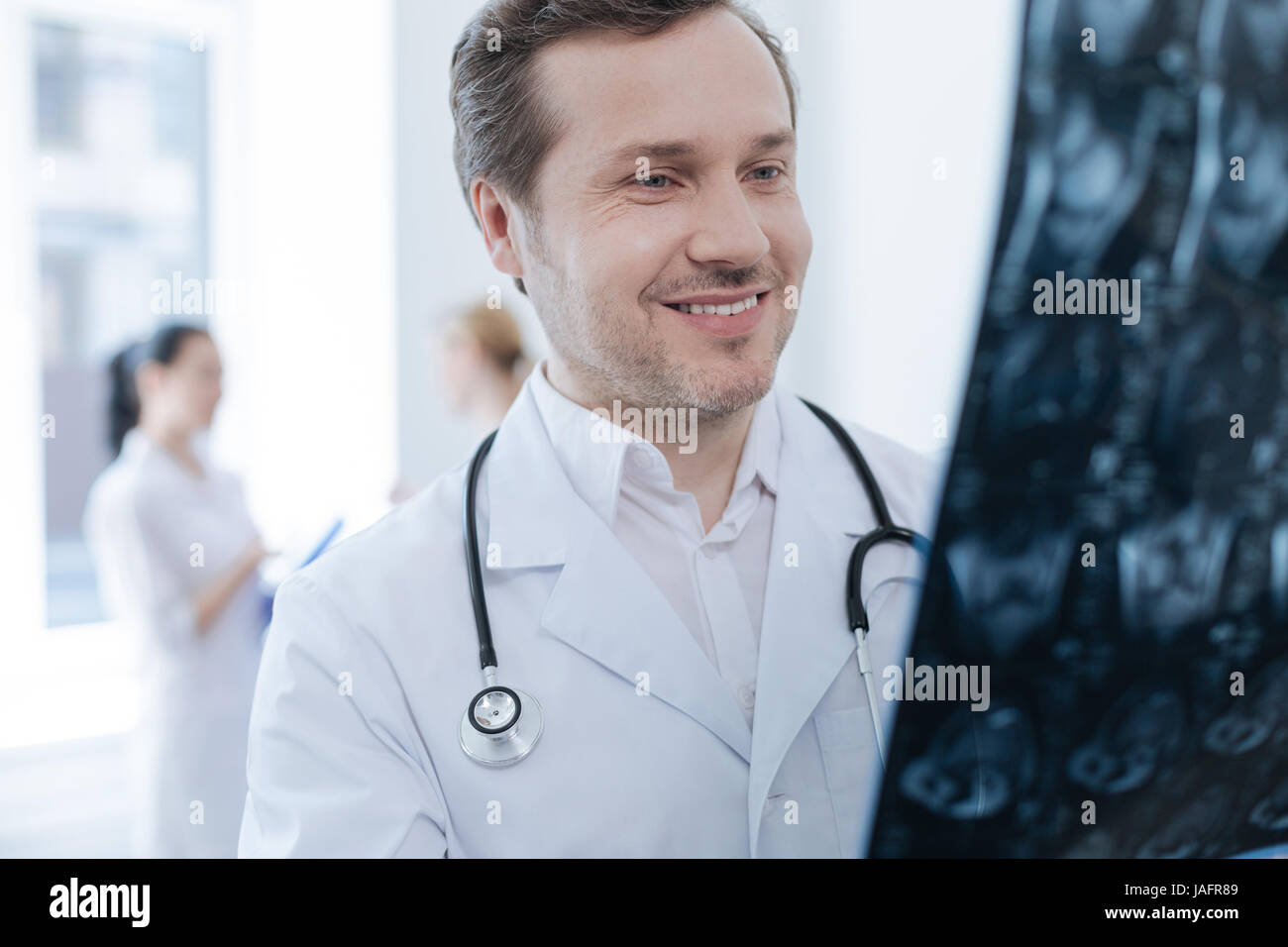 The moment of stating of diagnosis . Professional bearded smiling neurosurgeon working at the clinic and holding Stock Photo
