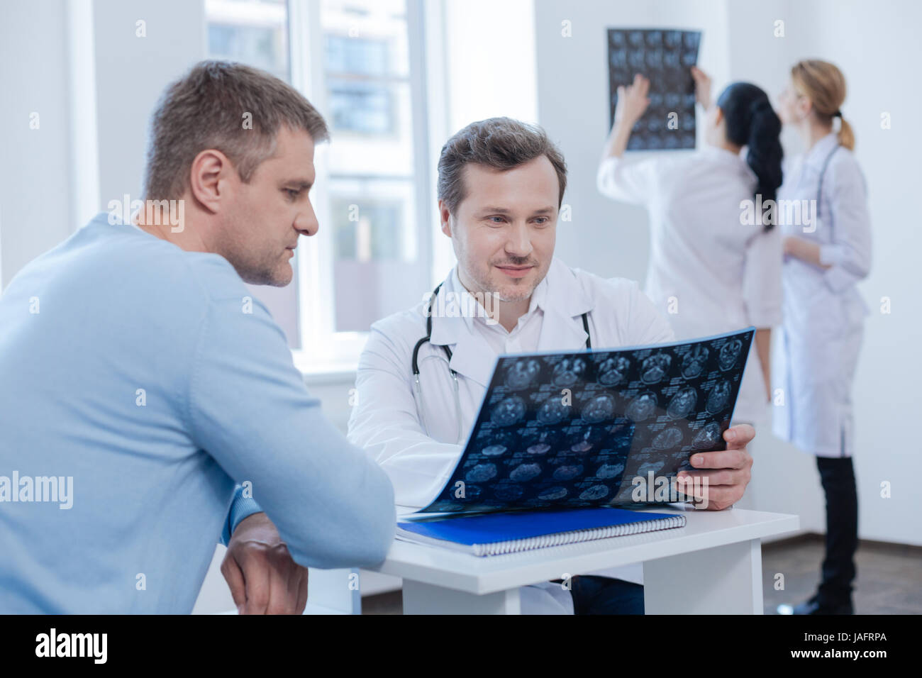 Explaining all details of treatment. Mature experienced confident therapist enjoying appointment with patient and Stock Photo