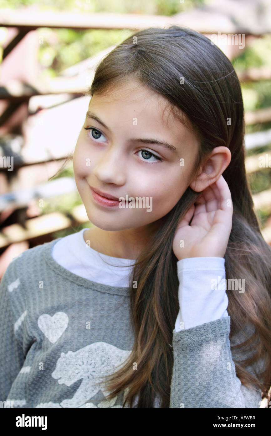 Young pre-teen kid with long hair. - Stock Image