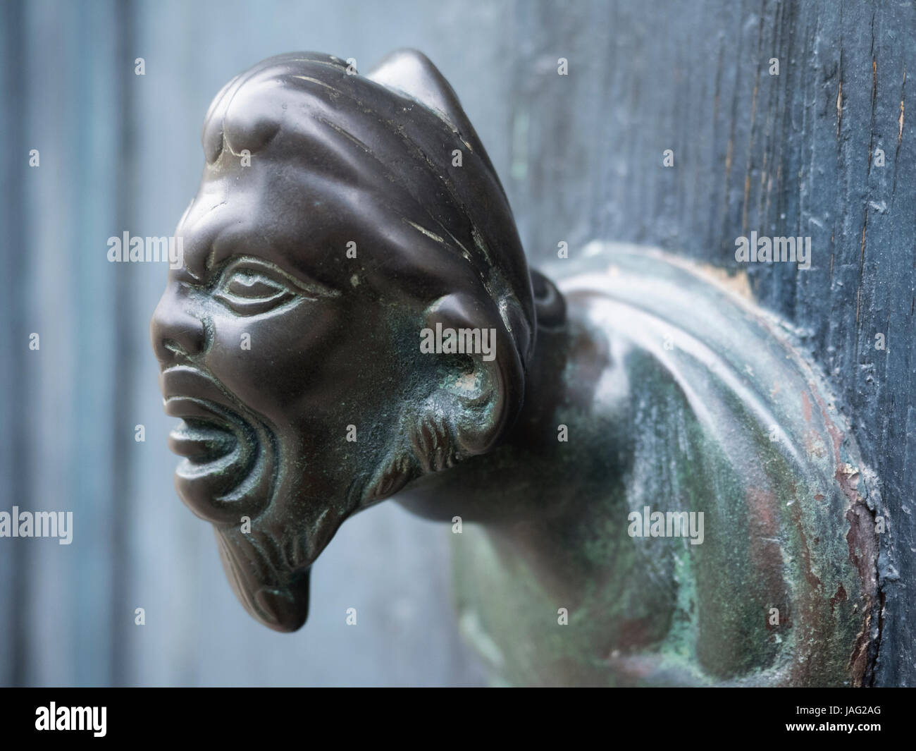 Venice. A metal handle or knocker, a human or goblin head grimacing with an open mouth. - Stock Image