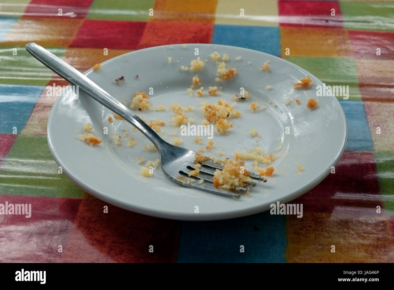 An empty small side plate with a fork and the crumbs left from a cake that has been eaten, sitting on a shiny tablecloth - Stock Image