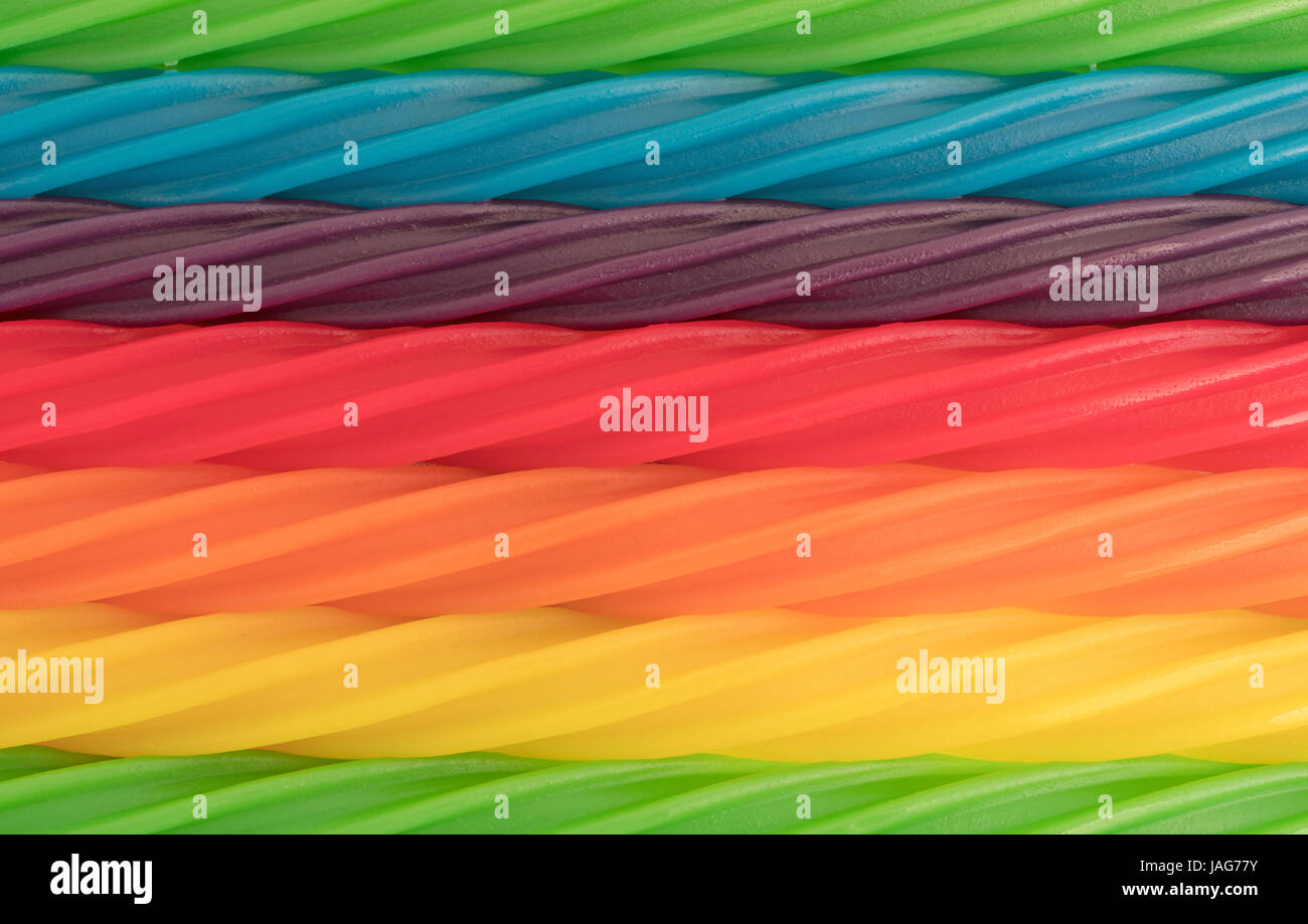 A very close view of colorful spiral licorice sticks in rows. - Stock Image