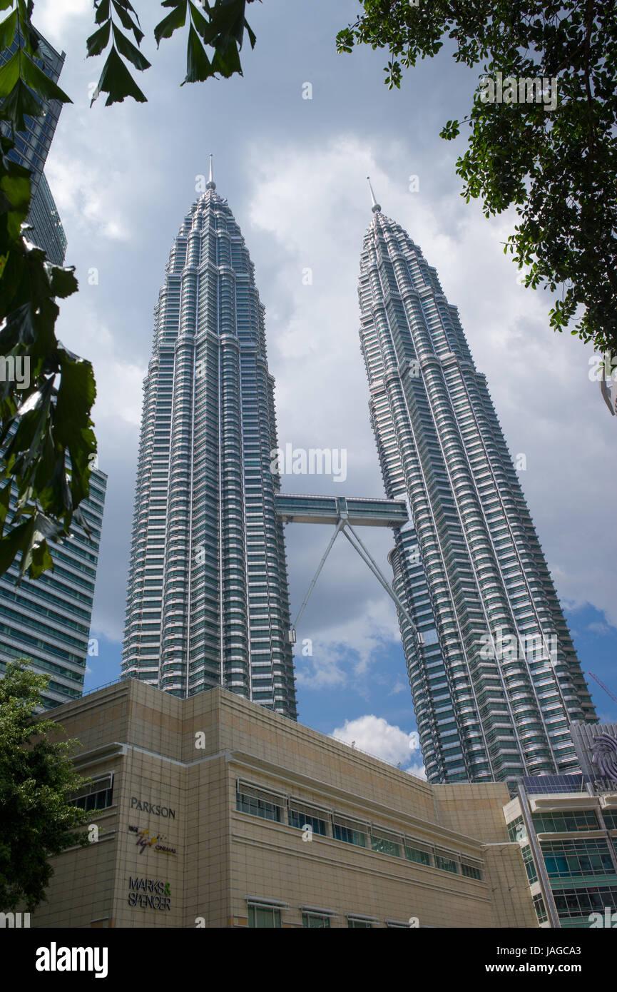 Petronas Twin Towers and skybridge ground level near KLCC shopping mall, Kuala Lumpur, Malaysia - Stock Image