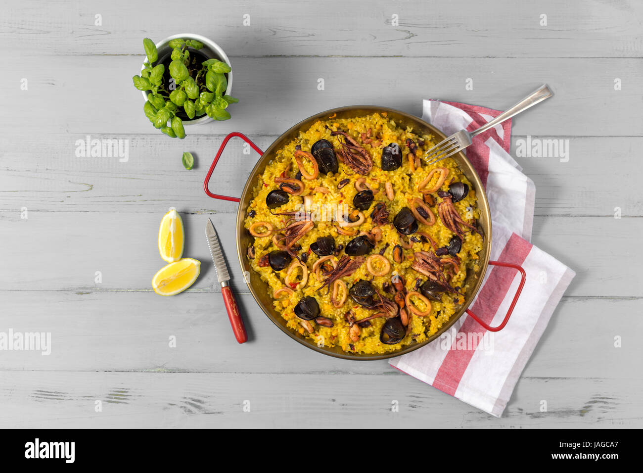 Seafood Paella in Traditional Pan on Rustic Wooden Table - Stock Image