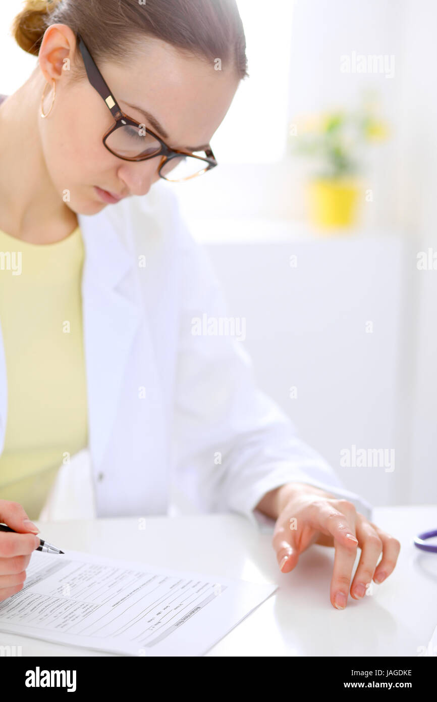 Close-up of a female doctor filling  out application form , sitting at the table in the hospital Stock Photo